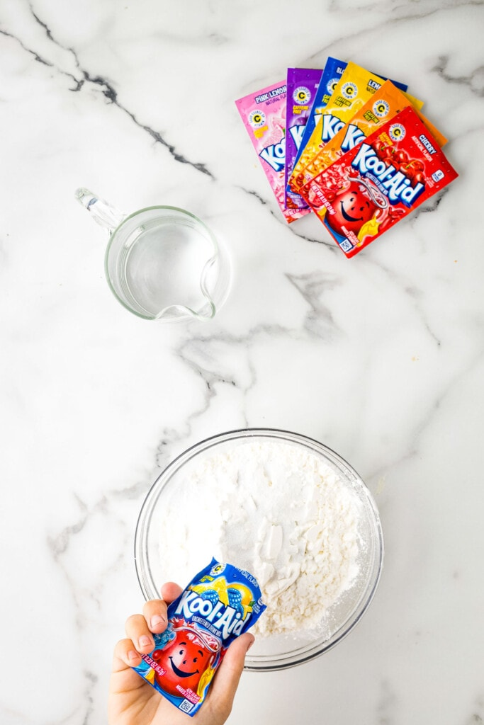 Pouring Kool-Aid Mix into a bowl of cornstarch