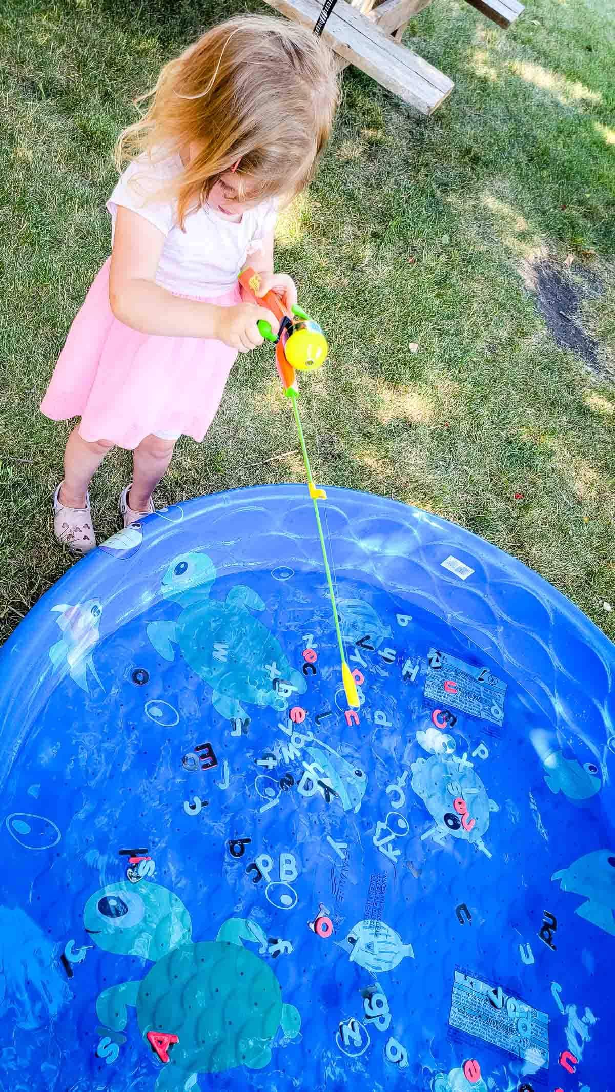 Little girl fishing for letters in kiddie pool