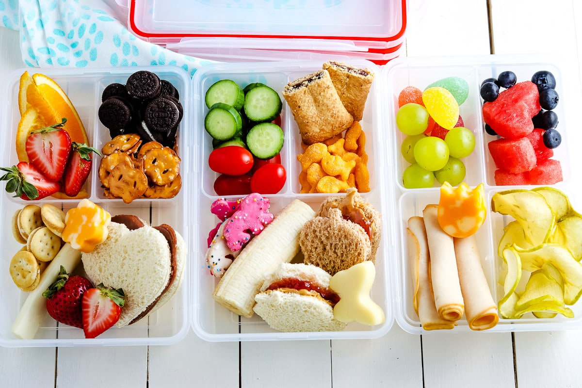Three lunch boxes filled with different foods