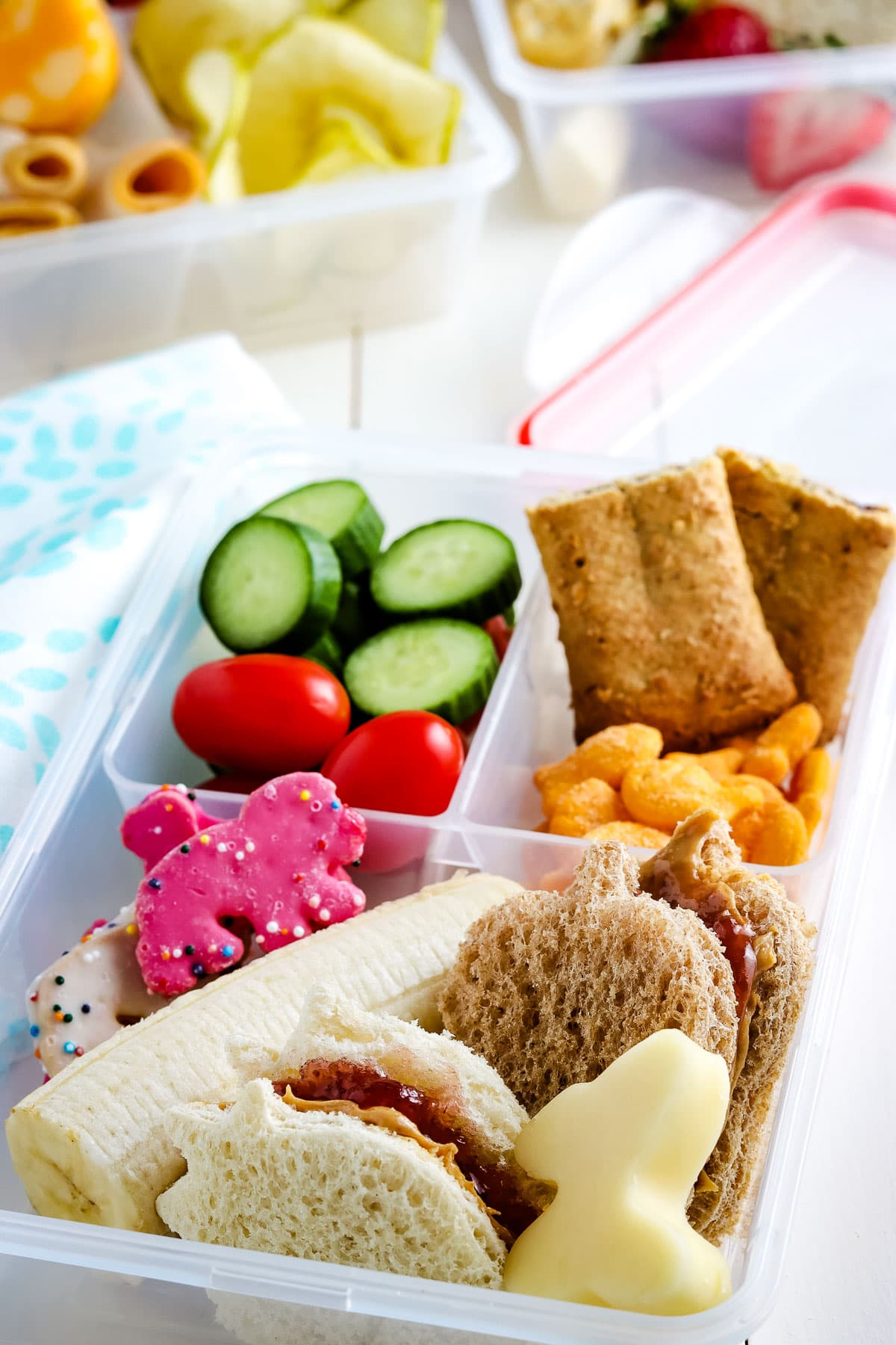 Lunch box filled with sandwich, cheese, granola bar, cucumbers, tomatoes and more