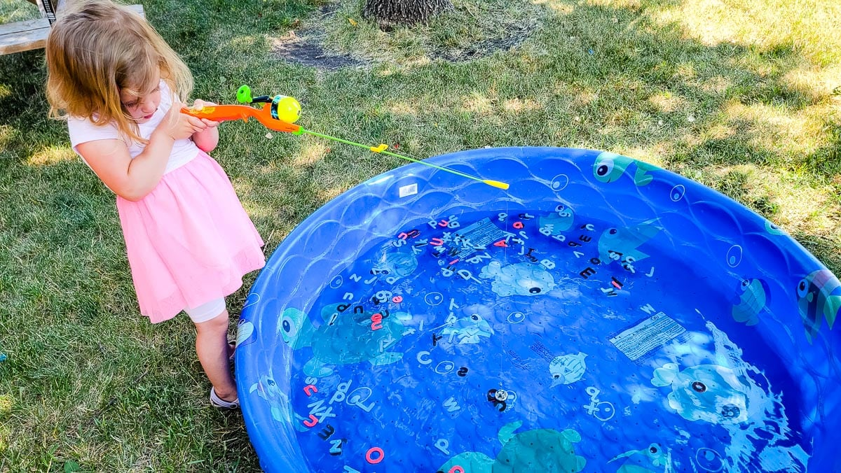 Kiddie pool with girl fishing for letters