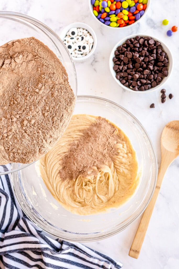 Adding dry mixture to cookie dough in glass bowls