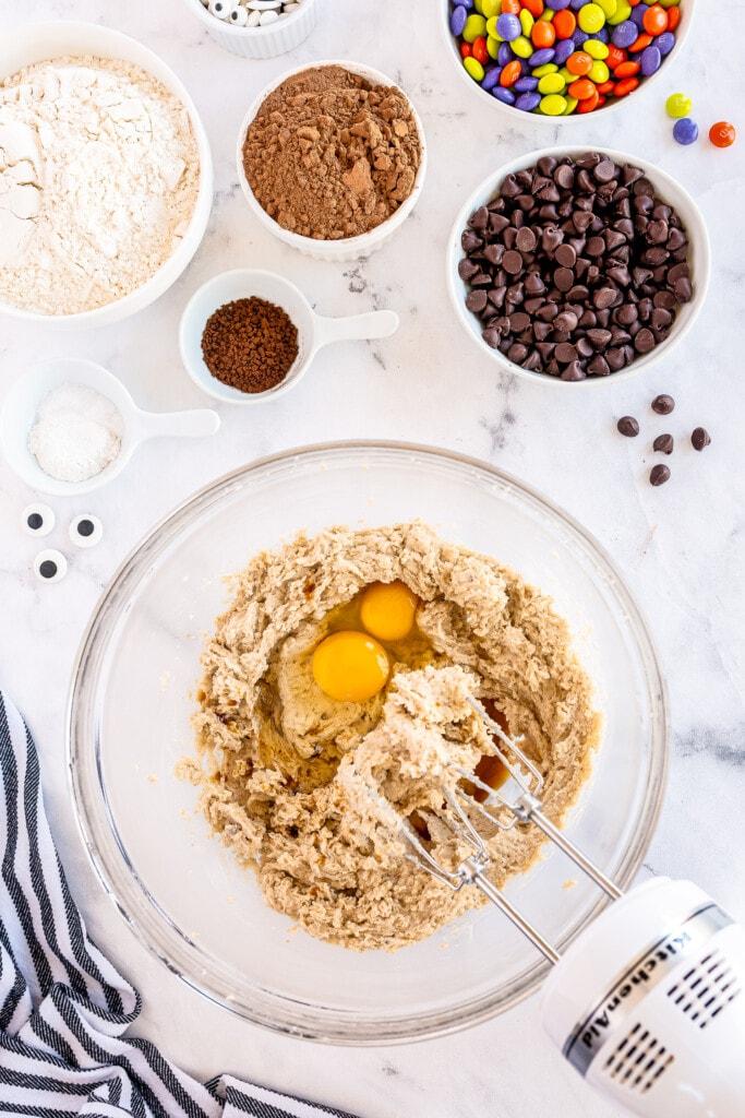 Hand mixer beating eggs into cookie dough