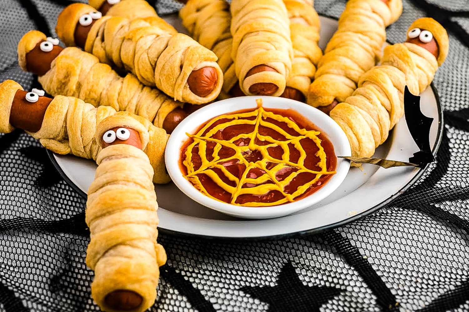 White plate with mummy hot dogs on it and ketchup with mustard spider web